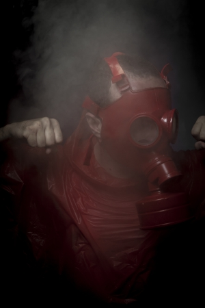 Nuclear, A man in a gas mask over  the smoke. black background and red colors Stock Photo - 24886249