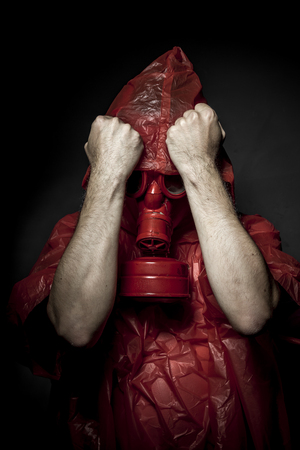 Ecology, A man in a gas mask over  the smoke. black background and red colors photo