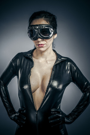 Beautiful woman dressed in black latex with glasses aircraft pilot photo