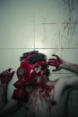 Crime scene, man with blood stains, nude with gas mask photo