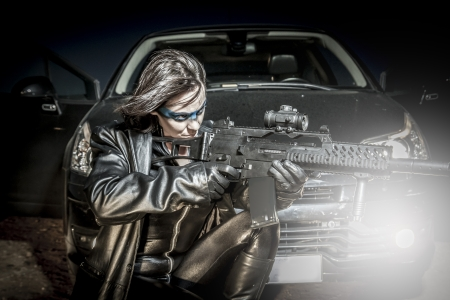 Dangerous woman dressed in black latex, armed with gun. comic style photo