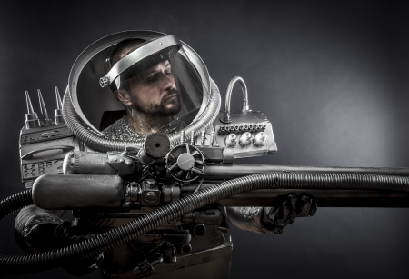 Cosmos, Astronaut on a black background with huge weapon. photo