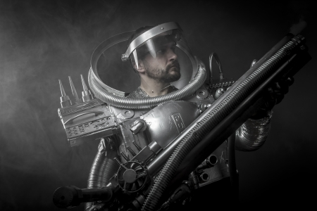 Cosmonaut, Astronaut on a black background with huge weapon. photo