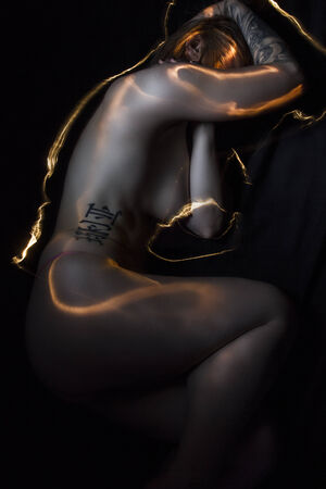 Light painting.Sexy tattoed woman, blonde gil with urban style. photo