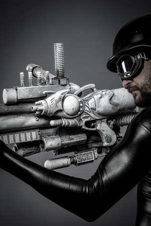 Gun.Starfighter with huge plasma rifle, fantasy concept, military helmet and goggles motorcyclist photo