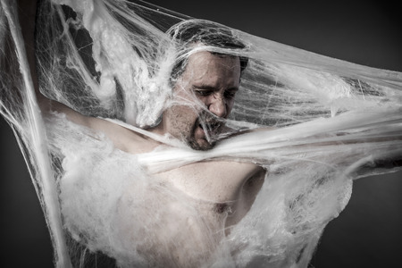 cobwebby: Danger. man tangled in huge white spider web Stock Photo