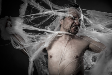 spider man: network. man tangled in huge white spider web Stock Photo