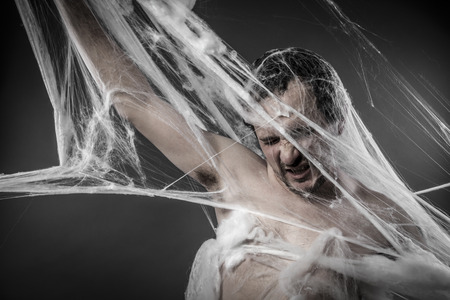 cobwebby: Arachnid.man tangled in huge white spider web Stock Photo