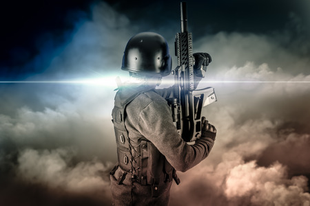 Soldier in uniform with rifle, assault sniper on apocalyptic clouds, firing photo