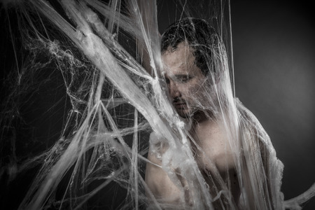 Internet.man tangled in huge white spider web Stock Photo