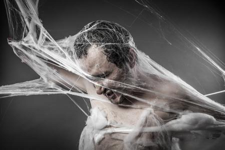 cobwebby: Spiderweb.man tangled in huge white spider web Stock Photo