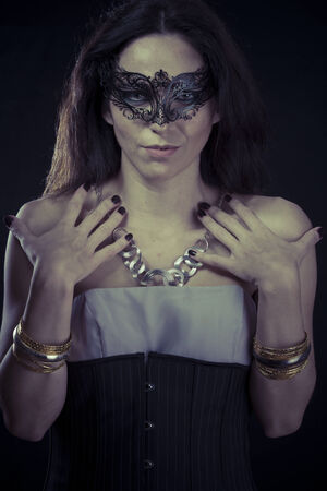 Sexy.Beautiful young woman in mysterious black Venetian mask. Fashion photo. tribal design. photo
