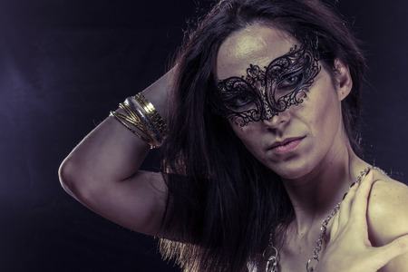 Beautiful young woman in mysterious black Venetian mask. Fashion photo. tribal design. photo