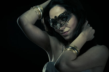 Tribal.Beautiful young woman in mysterious black Venetian mask. Fashion photo. tribal design. photo