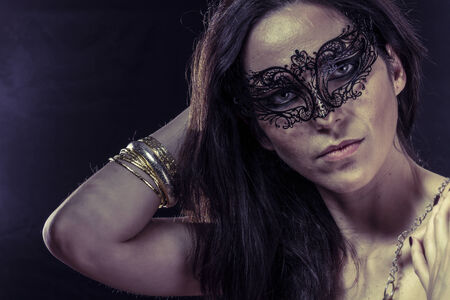 Lady.Beautiful young woman in mysterious black Venetian mask. Fashion photo. tribal design. photo