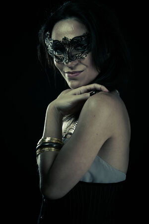 Tribal.Beautiful young woman in mysterious black Venetian mask. Fashion photo. tribal design. photo