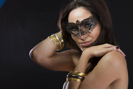 Sensuality.Beautiful young woman in mysterious black Venetian mask. Fashion photo. tribal design. photo