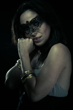 Mysterious.Beautiful young woman in mysterious black Venetian mask. Fashion photo. tribal design. photo