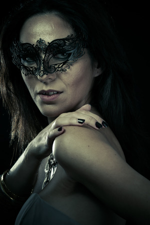Beautiful young woman in mysterious black Venetian mask. Fashion photo. tribal design. photo
