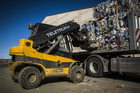 tractor loading piles of garbage in a truck