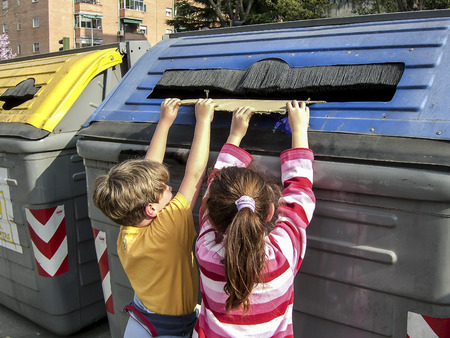 Children pulling a cardboard into recycling container for paper and paperboard