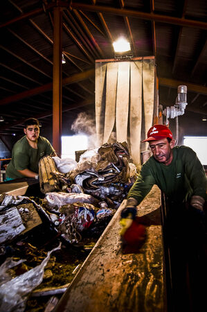 selection and separation of garbage, men and women working at recycling center