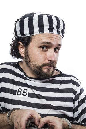 sentenced: Desperate, portrait of a man prisoner in prison garb, over white background Stock Photo