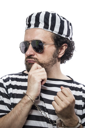 lawbreaker: Desperate, portrait of a man prisoner in prison garb, over white background Stock Photo