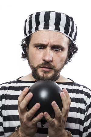 waiting convict: Funny man prisoner criminal with chain ball and handcuffs in studio isolated on white background