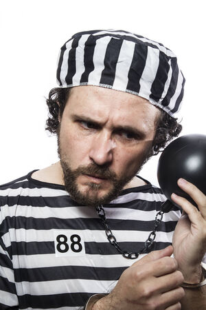 waiting convict: Fun, one caucasian man prisoner criminal with chain ball and handcuffs in studio isolated on white background Stock Photo