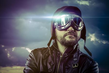 flight helmet: Flight, man dressed as pilot in helmet on clouds background. Vintage pilot (aviator) concept