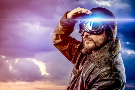 man dressed as pilot in helmet on clouds background. Vintage pilot (aviator) concept photo