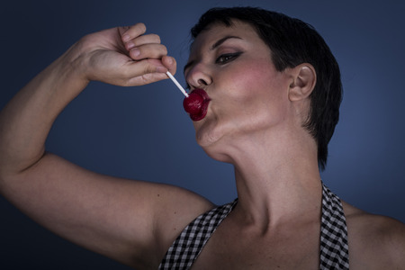 happy young woman with lollypop  in her mouth on blue background photo
