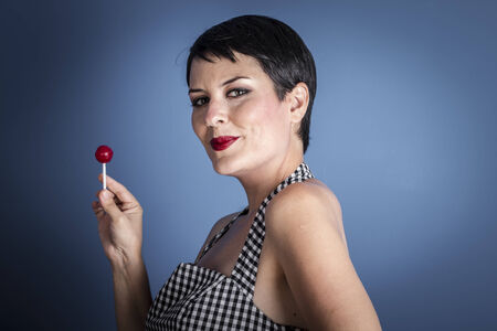 happy young woman with lollipop  in her mouth on blue background photo