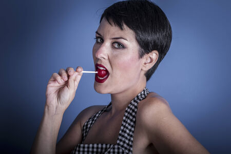 Candy, happy young woman with lollypop  in her mouth on blue background