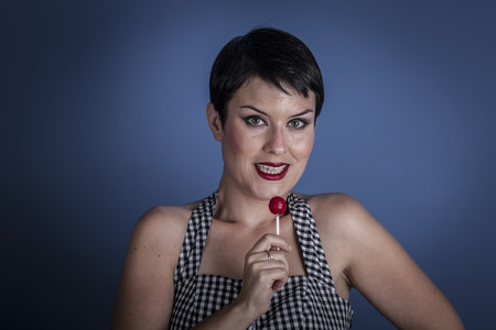Diet, happy young woman with lollypop  in her mouth on blue background photo