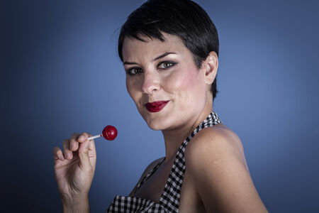 happy young woman with lollypop  in her mouth on blue background Stock Photo - 26837209