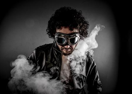 motorizado: Motociclista masculino sensual con las gafas de sol era vestido chaqueta de cuero, gran humo sobre fondo oscuro