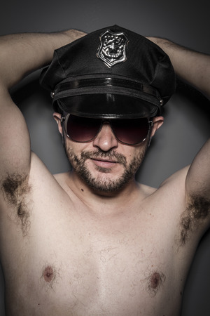 Good looking policeman, sexy police with sunglasses over dark background photo
