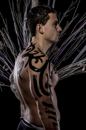 Tradition. Young attractive retro model in old-fashioned wild clothing Tribe. Tattoo. Native savage man photo