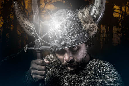 War, Viking warrior, male dressed in Barbarian style with sword, bearded photo