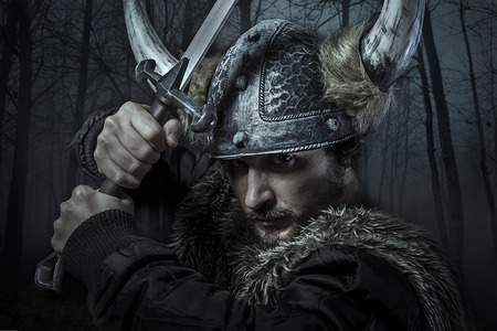 Viking warrior, male dressed in Barbarian style with sword, bearded