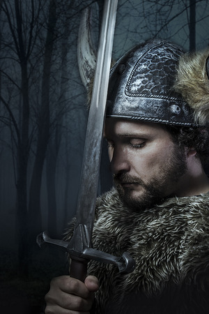 Peace, Viking warrior, male dressed in Barbarian style with sword, bearded photo
