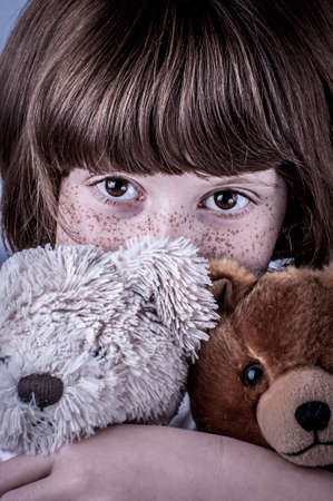 girl with freckles and two stuffed animals, teddy bears photo