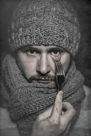 man with a fork in his eye, concept danger, risk photo