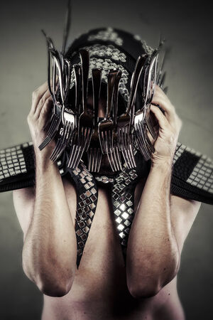 Man with helmet made ​​with forks and knives, artistic concept photo