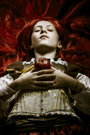 girl dressed in era with red apple in her hands photo