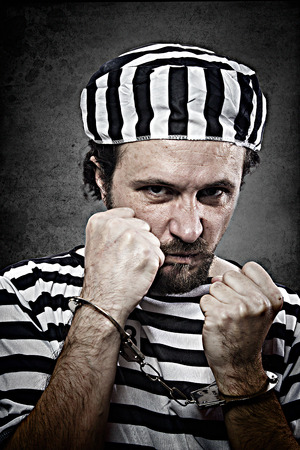 Desperate, portrait of a man prisoner in prison garb, over white background photo
