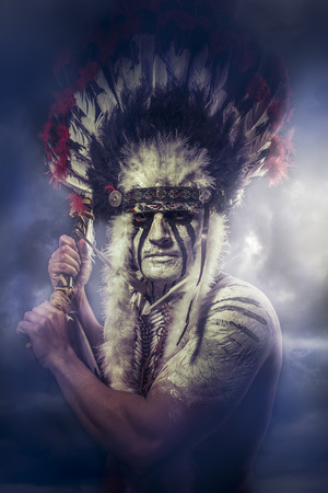 indio americano: Guerrero indio americano, jefe de la tribu. hombre con un tocado de plumas y tomahawk, nubes