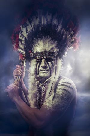 guerriero indiano: Guerriero indiano americano, capo della trib�. uomo con copricapo di piume e Tomahawk, nuvole Archivio Fotografico